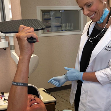 Dr. Brittany Westerman showing a patient his beautiful, clean smile