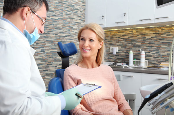 Woman talking to her dentist before getting a dental cleaning at Florence, AL